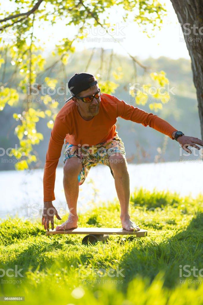 Bearded man is training on the balance board royalty-free stock photo