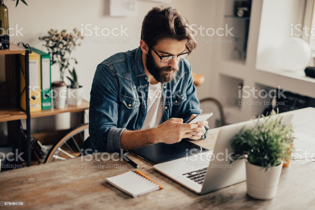 Bearded man is using his phone stock photo