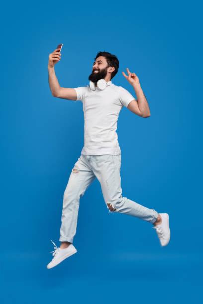 bärtige mann springen und nehmen selfie - mann bart freisteller stock-fotos und bilder