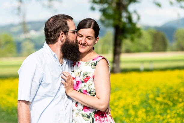 bearded man kissing his happy wife - brunette woman eyeglasses kiss man foto e immagini stock