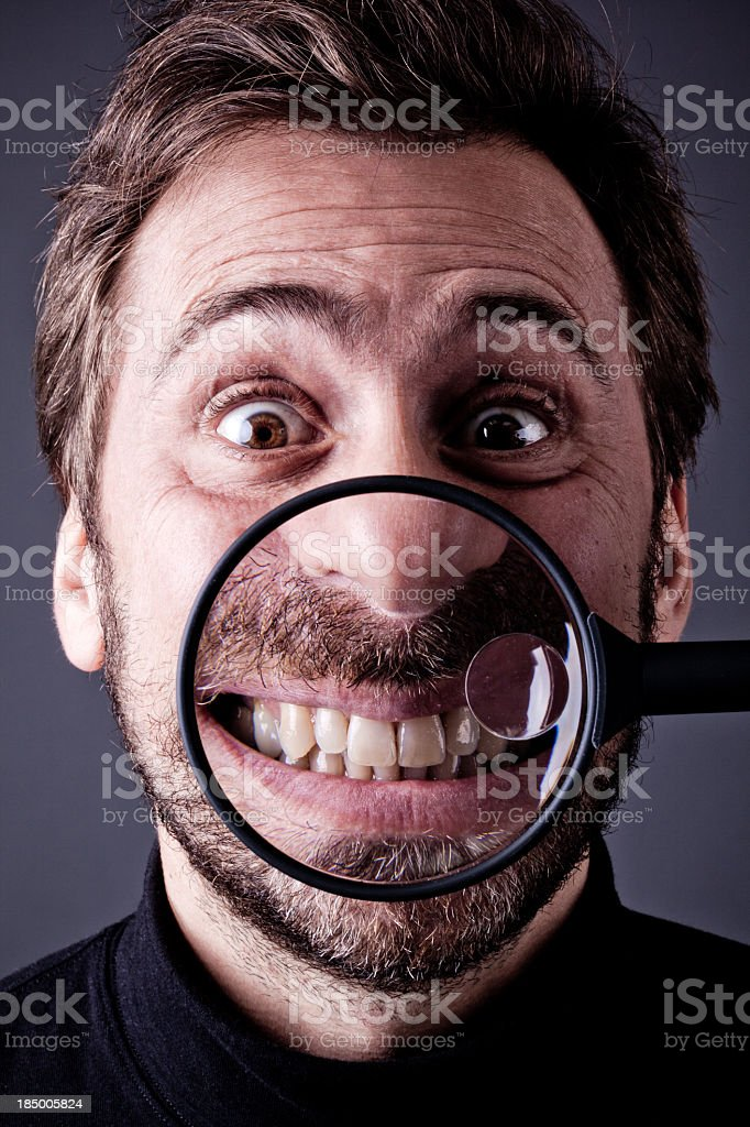 Bearded Man Laughing into Magnifying Glass stock photo