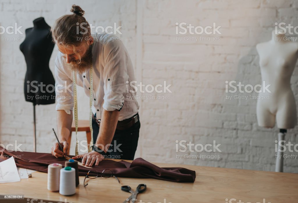 Bearded man leaning upon worktable stock photo