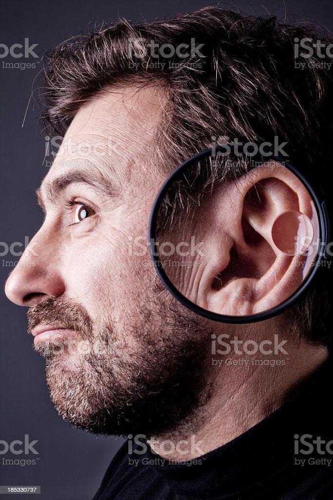 Uomo con barba ascolto in lente di ingrandimento - foto stock