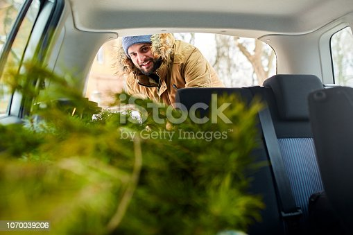 istock Bearded man loading christmas tree into the trunk of his car, inside view. Hipster puts fir tree into the back of his hatchback. Convertible auto interior with practical folding seats for boot space. 1070039206