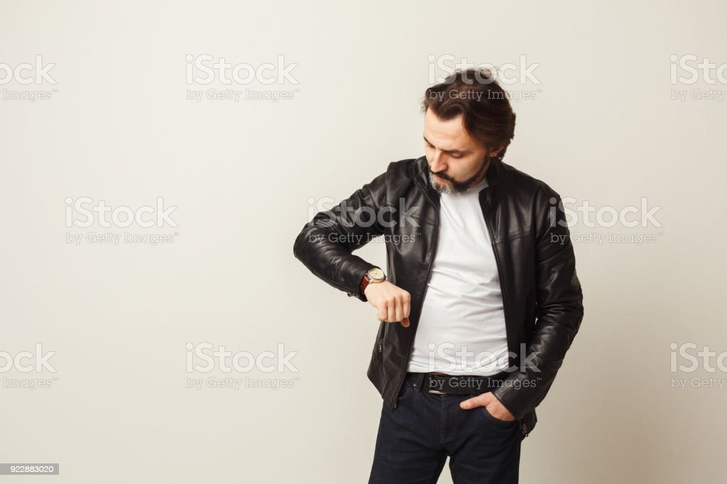 Bearded man looking at his smart watch stock photo