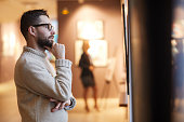 Side view portrait of mature bearded man looking at paintings while enjoying exhibition in modern gallery or museum, copy space