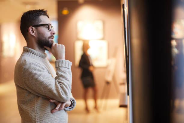 bearded man looking at paintings in art gallery - museu imagens e fotografias de stock