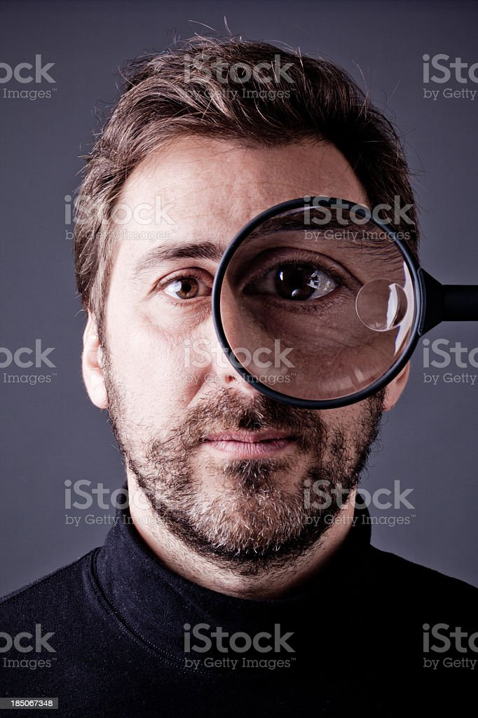 Bearded Man Looking into Magnifying Glass stock photo