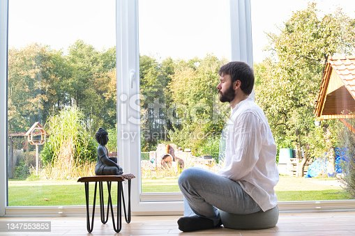 istock Bearded man meditating cross legged sitting on a pillow in front of a buddha statue. 1347553853