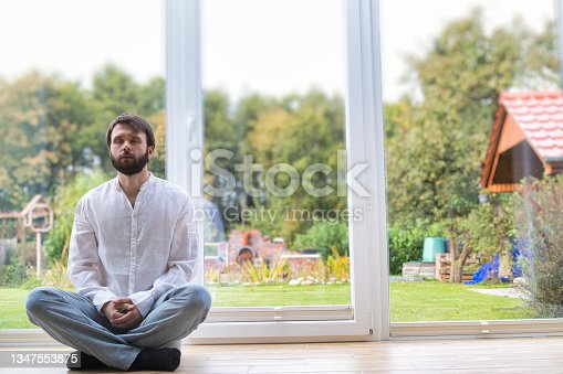 istock Bearded man meditating cross legged sitting on a pillow in front of a buddha statue. 1347553875