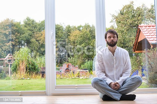 istock Bearded man meditating cross legged sitting on a pillow in front of a buddha statue. 1347553882