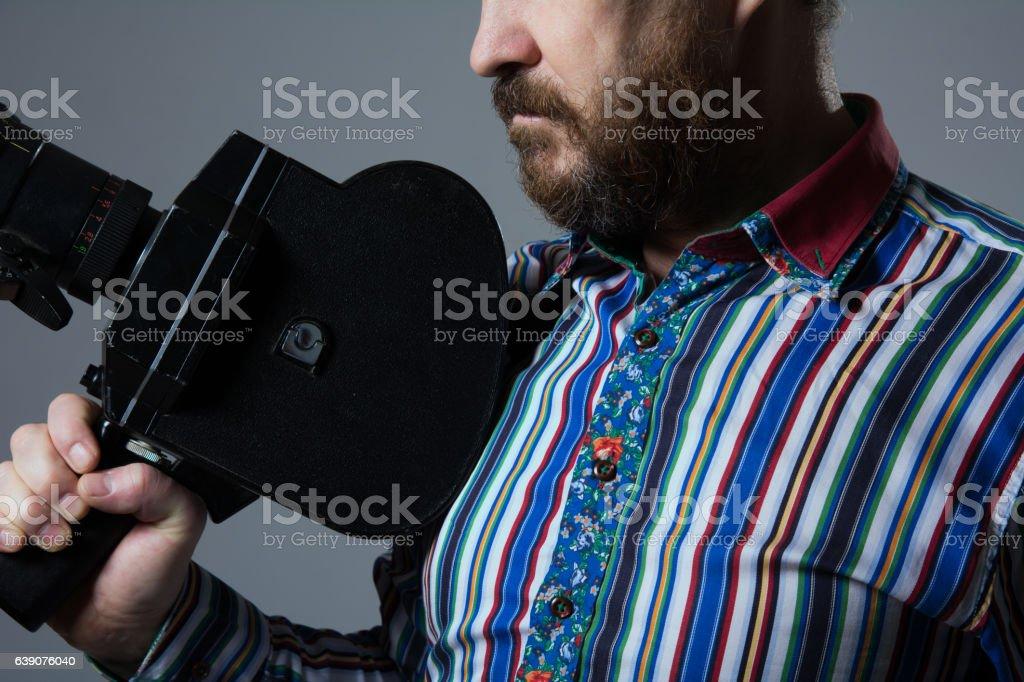 Bearded Man Movie Camera thoughtfully looks stock photo