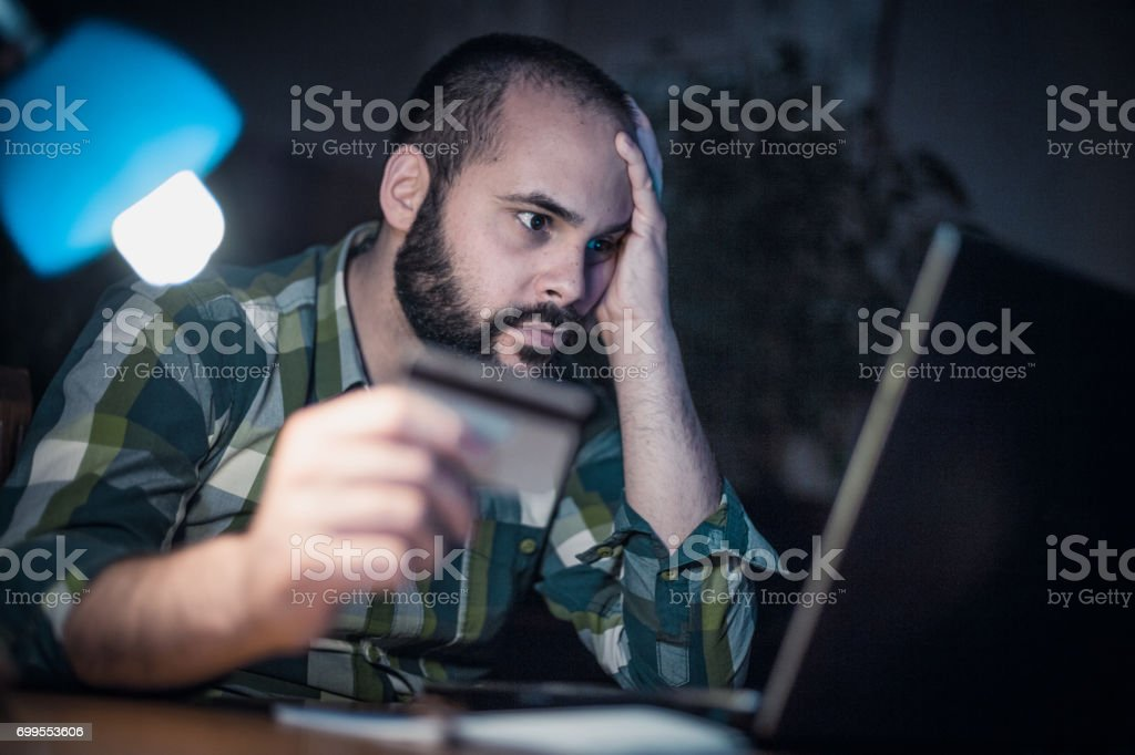 Bearded man paying with credit card from home at night stock photo