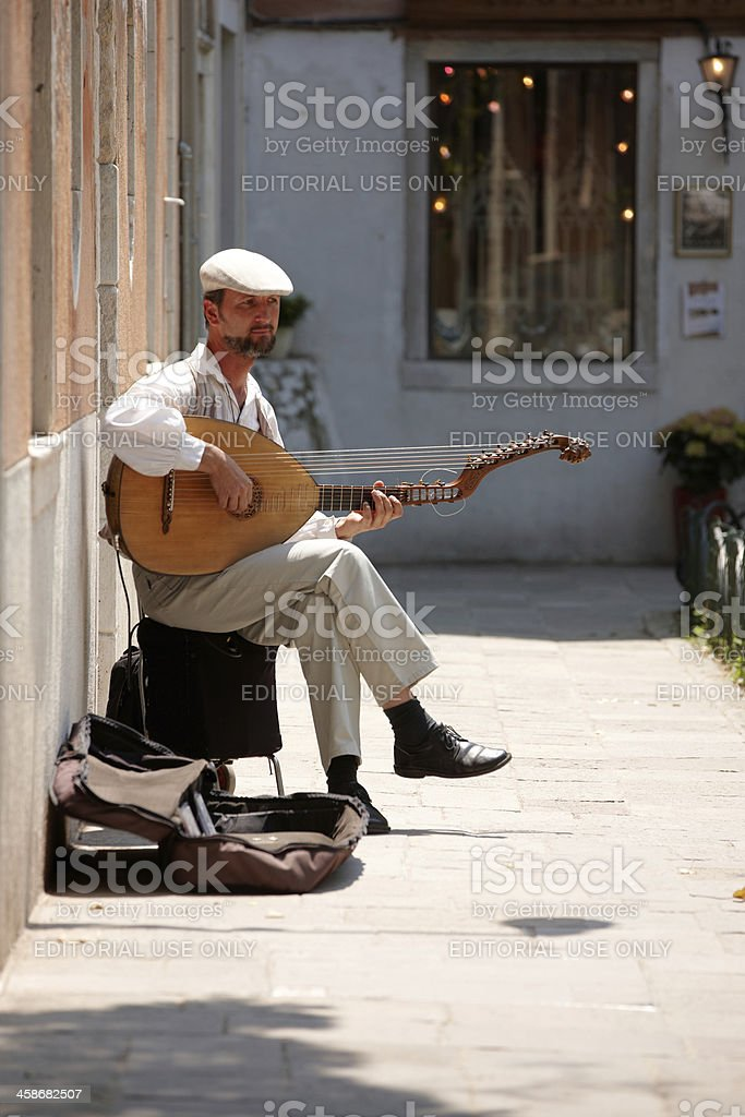Bearded man playing a lute in Venice side street royalty-free stock photo