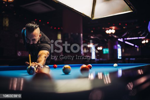 Young man with long beard playing snooker in a pub