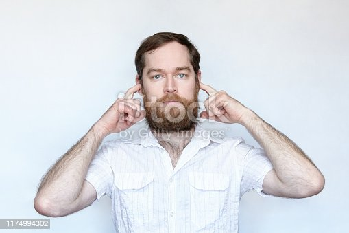 istock Bearded man plugging his ears with fingers 1174994302
