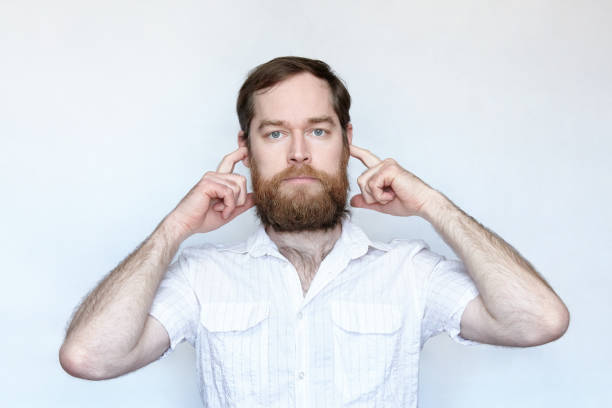 Bearded man plugging his ears with fingers stock photo