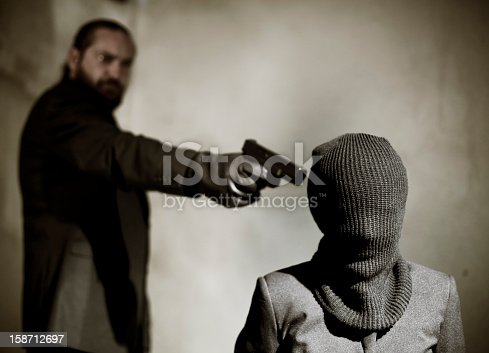 istock Bearded man pointing a gun at a man's temple to execute him 158712697