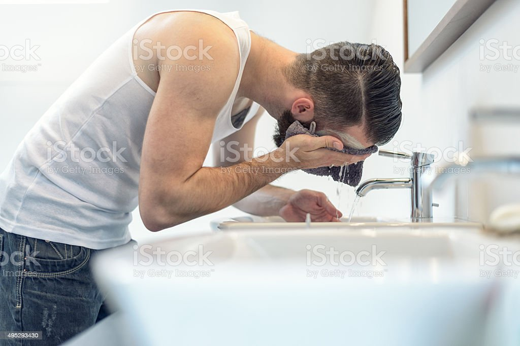 Bearded man rinsing his face in the bathroom stock photo