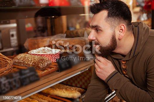 istock Bearded man shopping at the bakery 1200774078