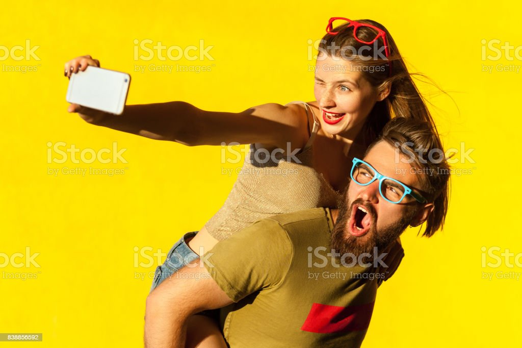 Grito de homem de barba, sardento piscadela de mulher morena, sorriso e fazendo o rapaz nas costas selfie - foto de acervo
