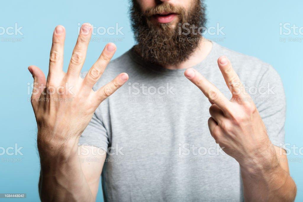 gesto de hombre show de la mano número siete cuenta con barba - foto de stock