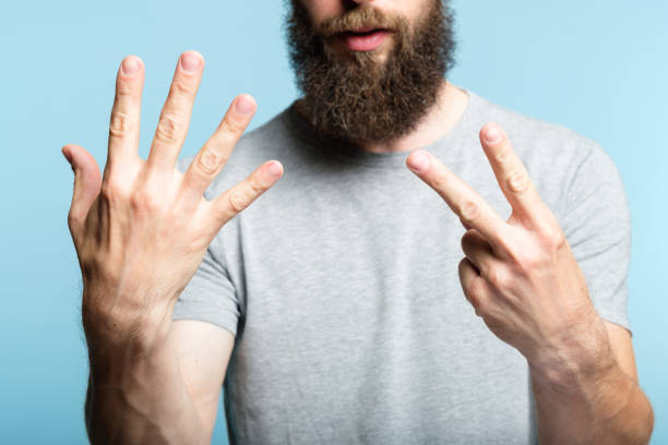 bearded man show hand number seven count gesture bearded man showing number seven with his hand. cropped shot of a male torso on blue background. casual hipster in grey t-shirt counting gesture. number 7 stock pictures, royalty-free photos & images