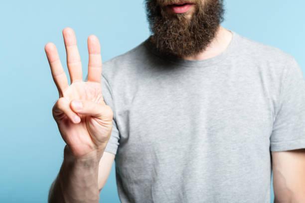 gesto de hombre show de la mano número tres cuenta con barba - foto de stock