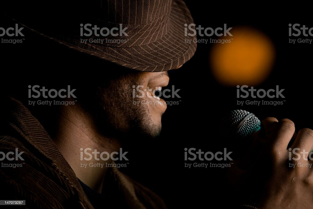 A bearded man singing with a hat over his eyes stock photo