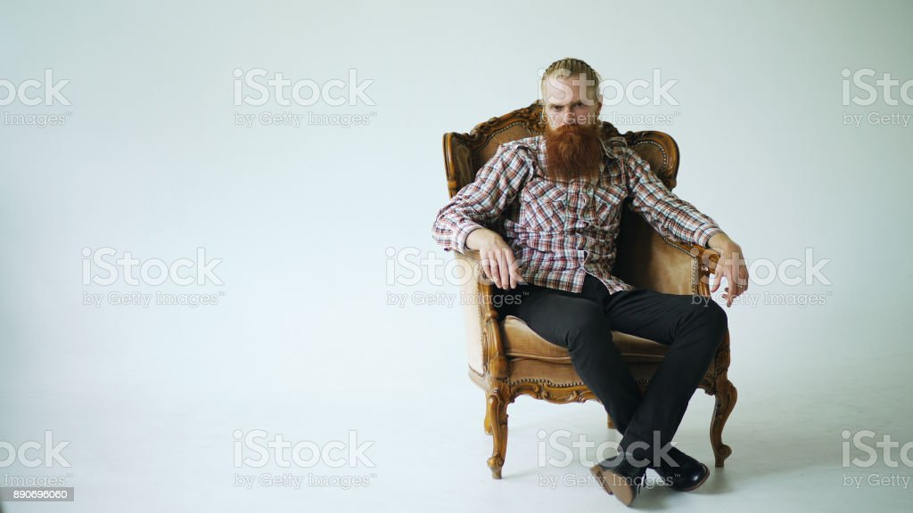 Bearded man sitting luxury armchair and looking into camera on white background stock photo