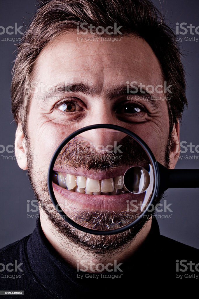 Bearded Man Smiling into Magnifying Glass stock photo
