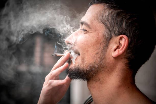 Homme barbu fumant un joint de marijuana - Photo