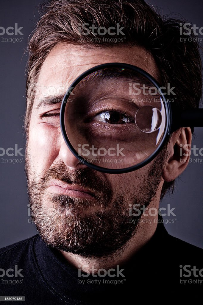 Bearded Man Snooping into Magnifying Glass stock photo