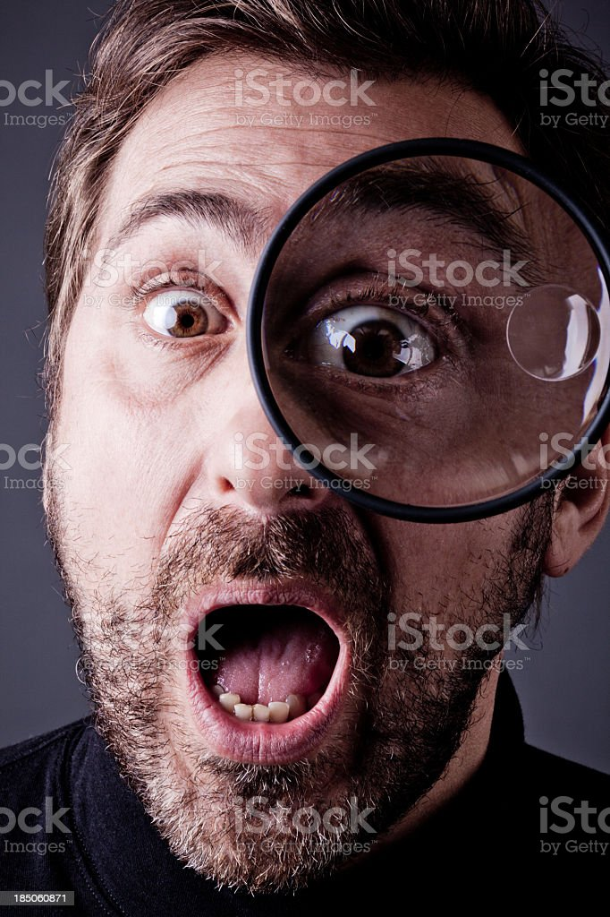 Bearded Man Surprising into Magnifying Glass stock photo
