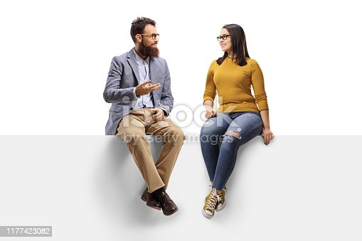 Full length shot of a bearded man talking to a young female seated on a banner isolated on white background