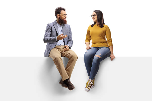 Bearded man talking to a young female seated on a banner Full length shot of a bearded man talking to a young female seated on a banner isolated on white background two people stock pictures, royalty-free photos & images