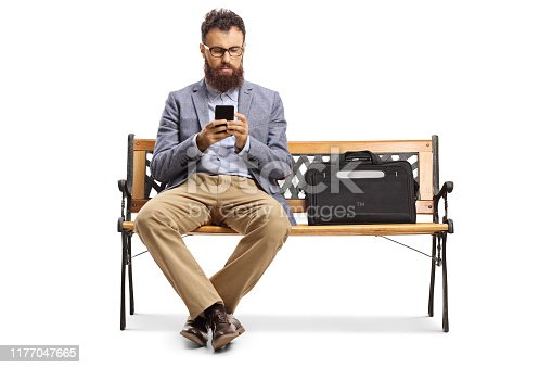 Bearded man typing on a mobile phone and sitting on a bench isolated on white background