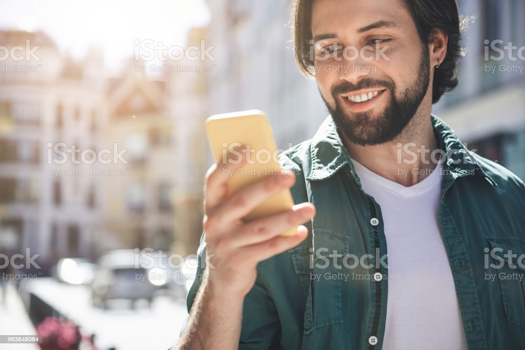 Bearded man using device outside - Royalty-free Adult Stock Photo