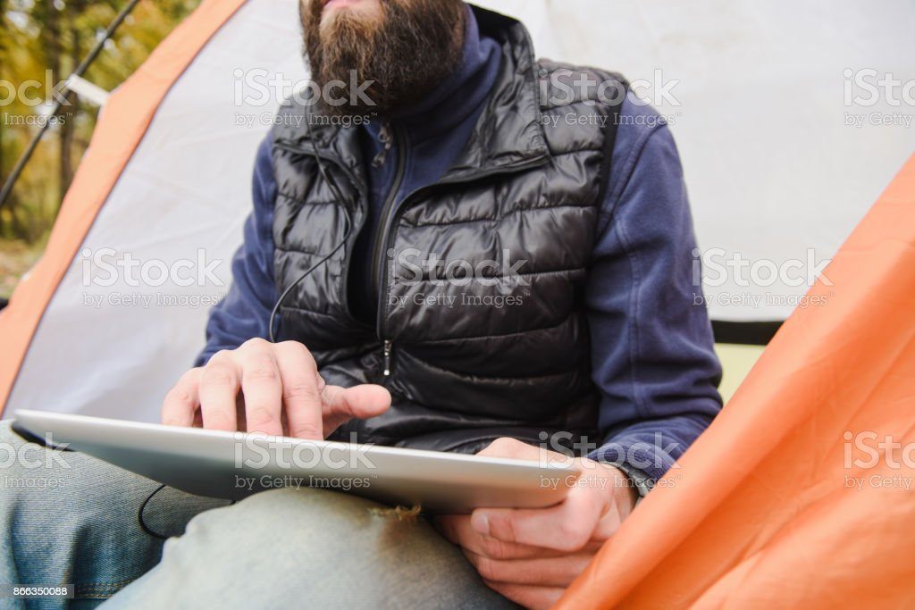 Bearded man using digital tablet in camping tent stock photo