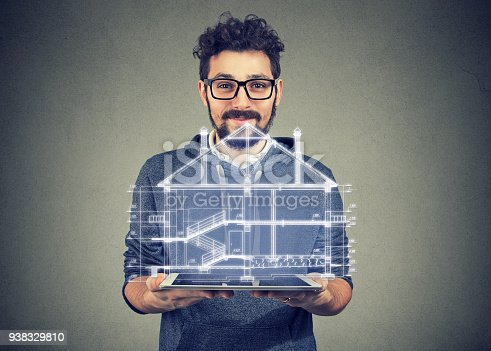 istock Bearded man using portable electronic pro tablet showing new home project 938329810