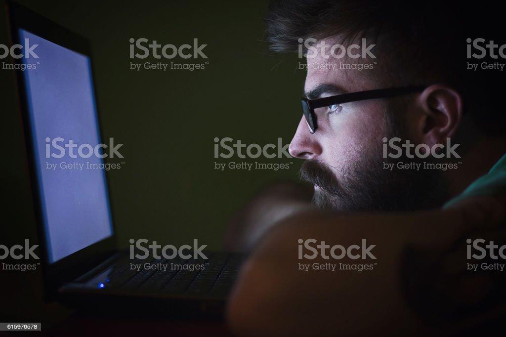 Bearded man using smart technology late night stock photo