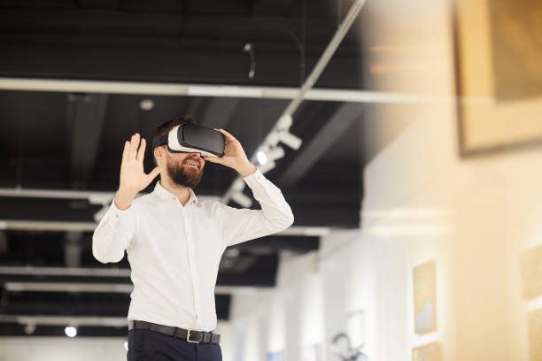 Bearded Man Using VR in Art Gallery stock photo