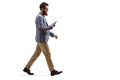 Full length profile shot of a bearded man walking and looking at his mobile phone isolated on white background
