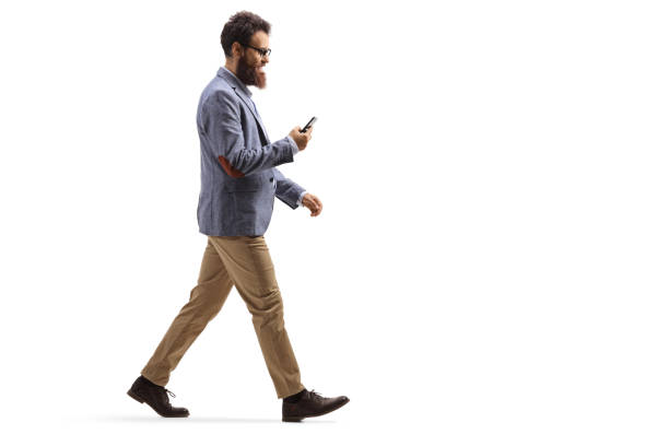 Bearded man walking and looking at his mobile phone Full length profile shot of a bearded man walking and looking at his mobile phone isolated on white background walking stock pictures, royalty-free photos & images