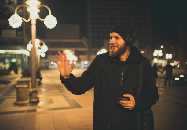 Bearded man walking on the street and waving stock photo