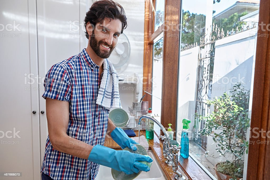 Bearded man washing dishes in a sink with gloves on stock photo