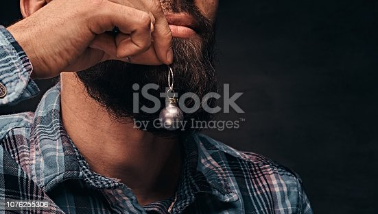 istock A bearded man wearing a checkered shirt holding a small christmas toy in the background of his face. 1076255306