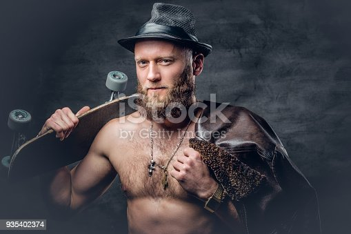 istock Bearded man wearing a leather jacket on naked torso. 935402374