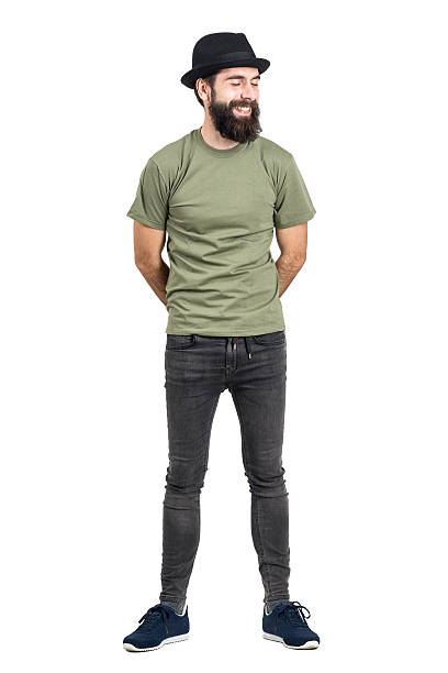 Bearded man wearing hat laughing carefree with eyes closed Bearded man wearing hat and t-shirt laughing carefree with eyes closed. Full body length portrait isolated over white studio background. men in tight jeans stock pictures, royalty-free photos & images