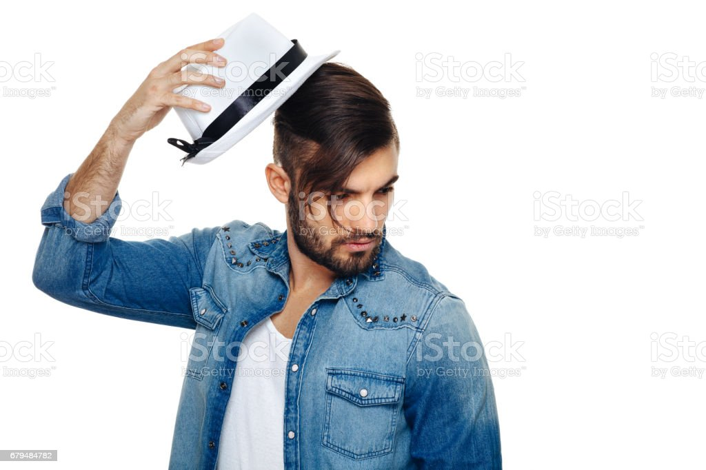 Bearded man with a hat posing in the studio royalty-free stock photo